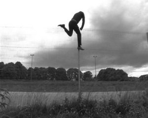 Black and white photograph of a man climbing over a fence.