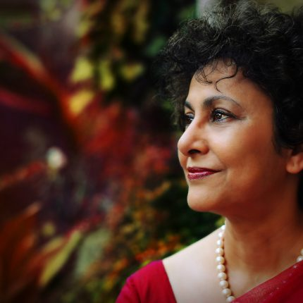 Jamie Wilson, Irene Khan (2014). Image courtesy of photographer. Photograph of side profile of a woman (Irene Khan) with plants in the background.