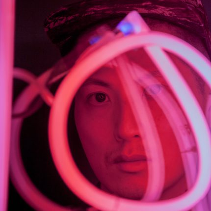 Photograph of artist Samson Young looking through a circular pink neon light.