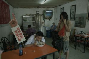 Man sat at table eating noodles with placard to the left of him. Next to the table a man dress in t-shirt and shorts is playing a harmonica.