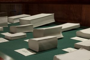 A display of porcelain books of various sizes, placed on a green surface.