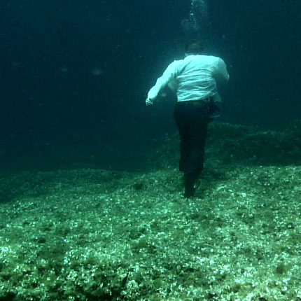 Man dress in white shirt and black trousers walking on a seabed.