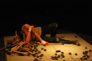 Photograph of artist Li Binyuan on a raised platform lying on his side looking exhausted, next to him are hammers. There are also broken hammers in front of him.