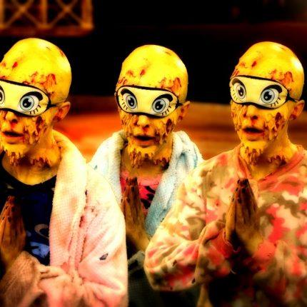 4 yellow faced figures with wearing eyemasks (with pictures of eyes on the masks) stand with their hands together as if praying.