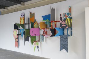 Painted pieces of wood attached to a wall, with some pieces protruding from the wall.