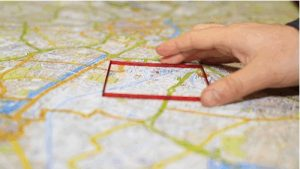 A hand holding an outline of a red square, which is being held on a map.
