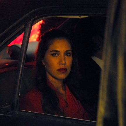 Photograph of a woman sat in the back of car looking through the opened window.