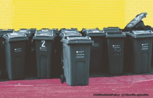 Print of wheelie bins against a yellow background and stood on a pink ground.