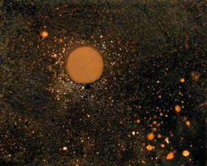 Black background with star like orange specks on it and one larger orange planet like circle.