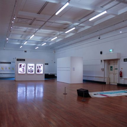 Gallery photograph. In the distance are 3 lightboxes of 3 people's faces. On the right is an artwork on material which is draped on the floor.