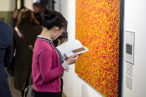 Woman holding brochure in front of an abstract yellow and red painting.