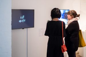 Two woman watching a video installation piece. The screen is black with small white hand-drawn figures and symbols on it.