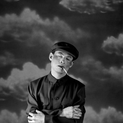 Black and white photograph. A man dress in a uniform with a cigarette hanging from the side of his mouth, stands with cross arms across his body and his eyes shut. The background depicts images of clouds.