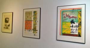 Photograph of three framed prints on a white gallery wall.