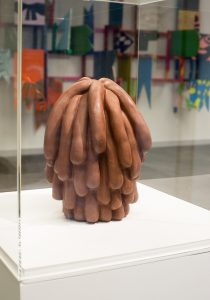 Terracotta sculpture in perspex display box. The sculpture looks like a pile of sausages.