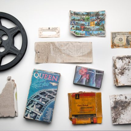 Photograph of what appears to be disregarded objects, including an American Dollar, a film reel, a photographic slide and a Queen concert ticket.