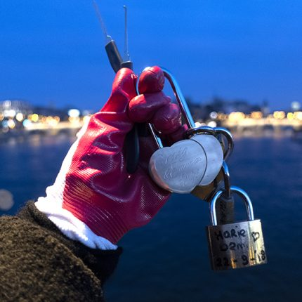 A gloved hand holding two 'love locks' and a padlock.