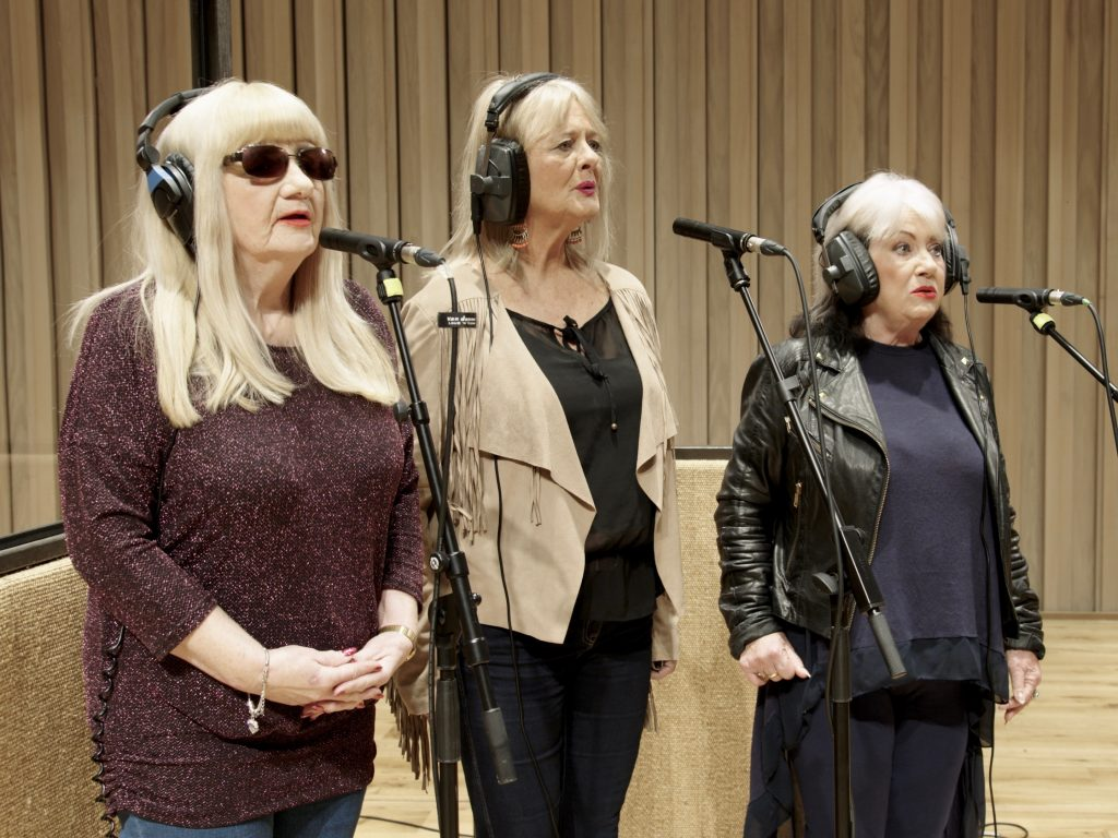 A film still of three women stood singing at microphones.