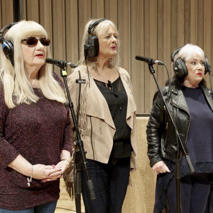 A film still of three women stood singing at microphones.
