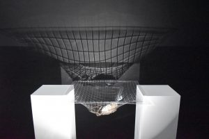 An image of the artists' work. Two white plinths stand almost a metre apart, with a clear square plastic sheet between them. The sheet has some unspecified objects in it's centre, and a grid pattern across it. A light source shines through the sheet, making a large shadow of the grid on a dark wall behind.