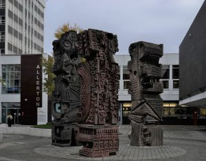 """A photograph of the outdoor sculpture """"untitled"""" by William Mitchell. The work consists of three grey cast concrete columns, each a few metres high, stood in a close group in a courtyard. They have various bold shapes, patterns and lines inscribed."""