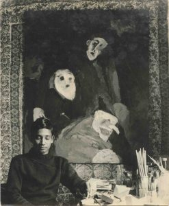 A black and white photograph of African-Indian artist Albert Adams, likely in his 20s at the time, sat in front of a large semi abstract, semi figurative painting in the studio.