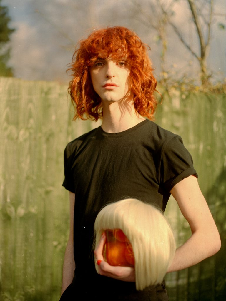 an artists photograph of a person who identifies as queer. The person has medium length red hair, a black tshirt, and they are holding a blonde wig. They are looking calmly towards the camera. They are stood outdoors.