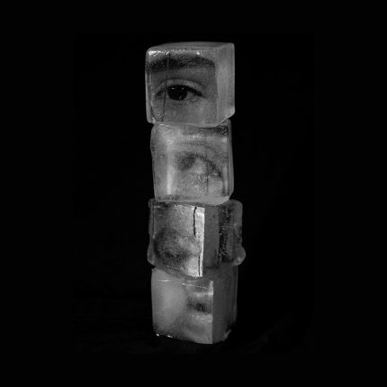 a contemporary artwork image. It shows a stack of 4 ice cubes against a solid black backgroun. Superimposed on or in the ice cubes are black and white images of human eyes and facial features
