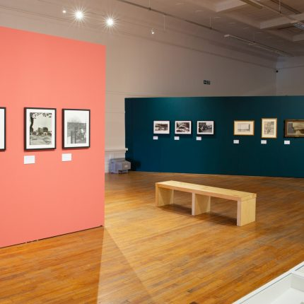 Interior photo of a gallery exhibition. The image shows a pink wall and a green wall, with small framed artworks hung on them.